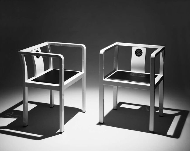 Empty chairs and table against wall