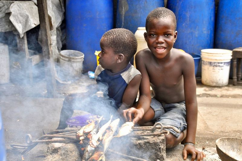 Two boys prepare fish on a grill