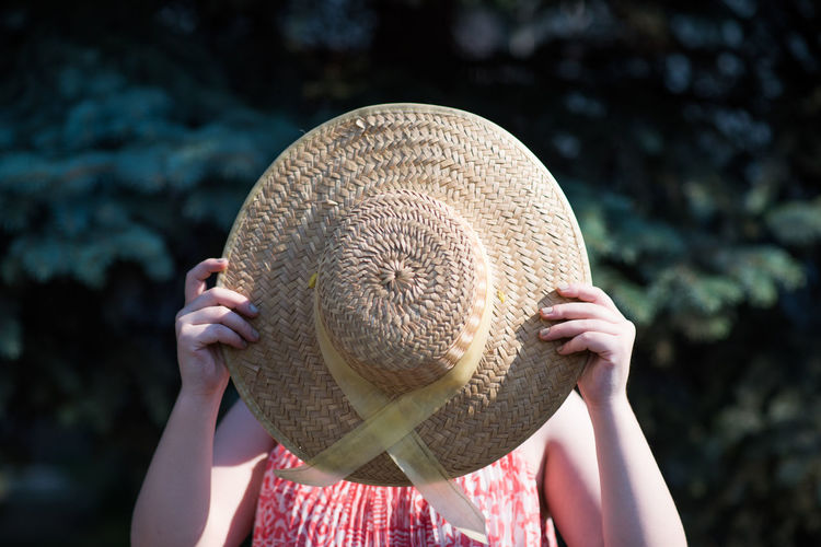 Woman holding sun hat on sunny day