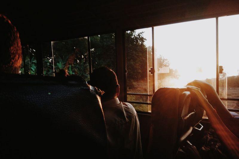 Man sitting in bus during sunset