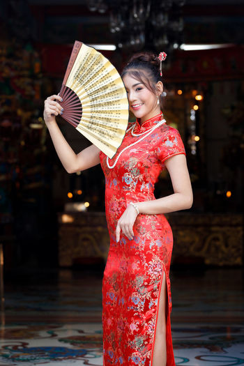 Midsection of woman holding red umbrella against blurred background