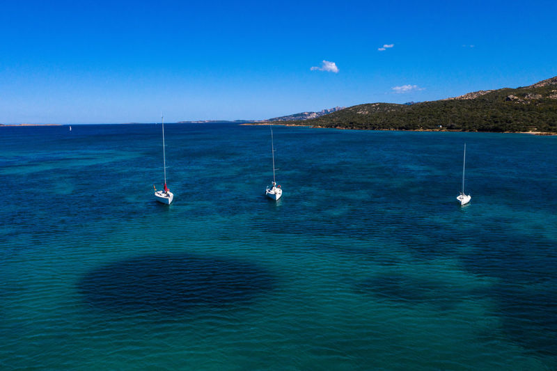 Sailboats in sea against blue sky
