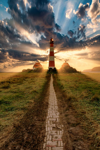 Lighthouse amidst field against sky during sunset