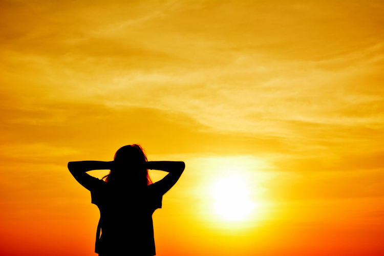 Silhouetted woman standing against orange sky