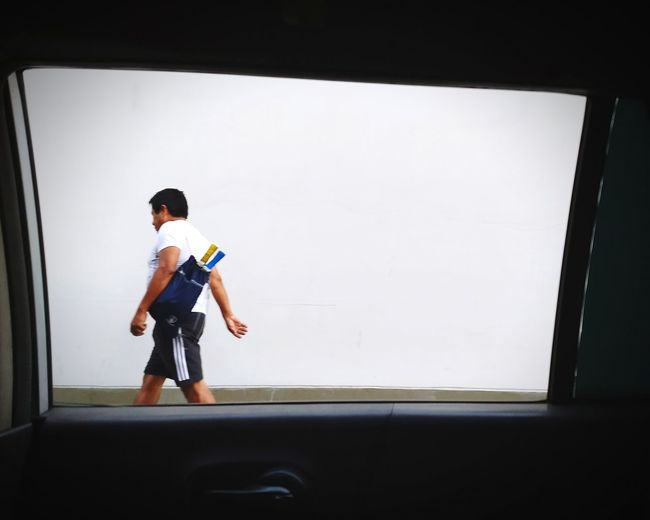 Full length of a boy looking through window