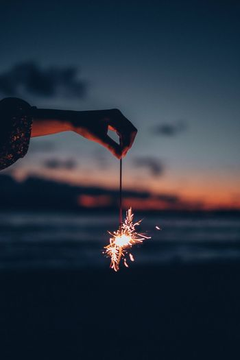 Cropped hand holding burning sparkler against sky during sunset
