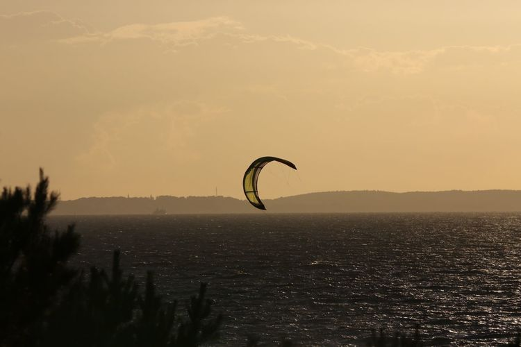 High angle view of parasail over sea against sky during sunset