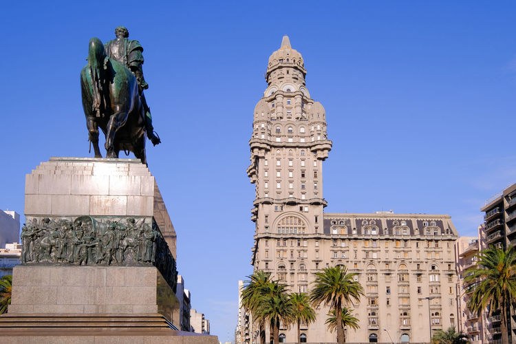 Low angle view of statue of historic building against clear sky