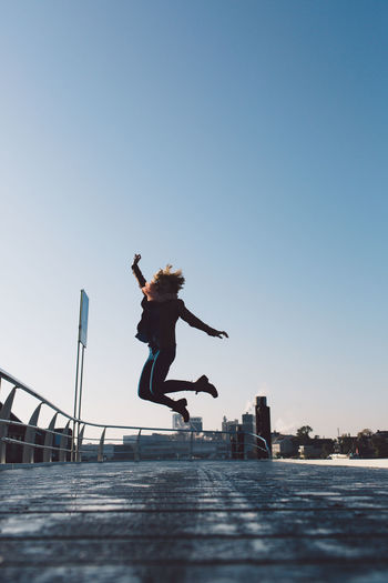 Woman jumping over promenade in city against clear sky