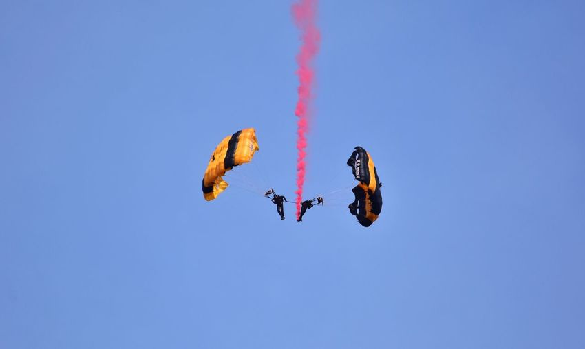 Low angle view of paragliders paragliding during airshow