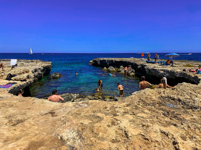 People on rocks by sea against blue sky