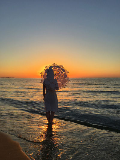 A woman with a vintage umbrella on a beach at sunset Nature Romantic Wait Woman Beach Beauty Dancer Horizon Over Water Sea Staring Summer Sun Sunrise Sunset Umbrella Vintage Warm Water