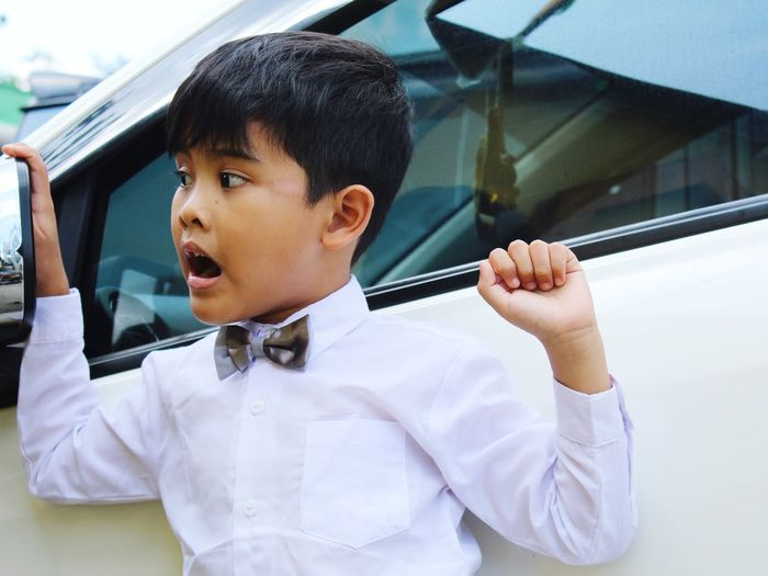 Boy looking away while sitting in car