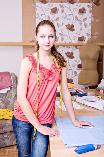 Portrait of young woman standing by table in workshop