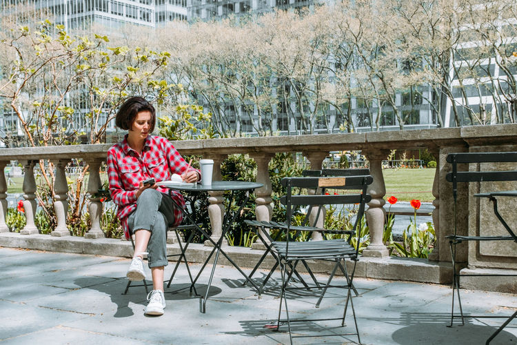 Young woman writing in personal diary and drinking coffee while waiting for her friend in the park