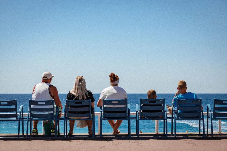 Rear view of family sitting on chairs at beach against clear blue sky