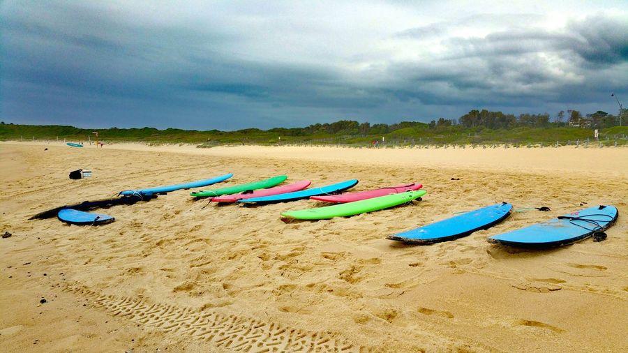 Multi colored sand on beach against sky