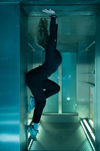 Side view of woman stretching against window