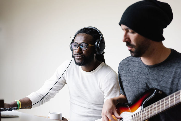 Man playing guitar while friend listening through headphones