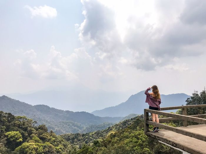 Woman standing at observation point over mountains against sky