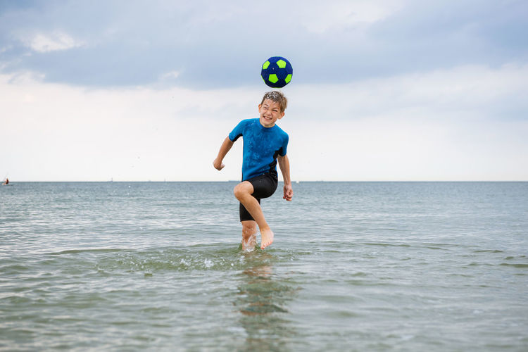 Cheerful boy playing with ball in sea