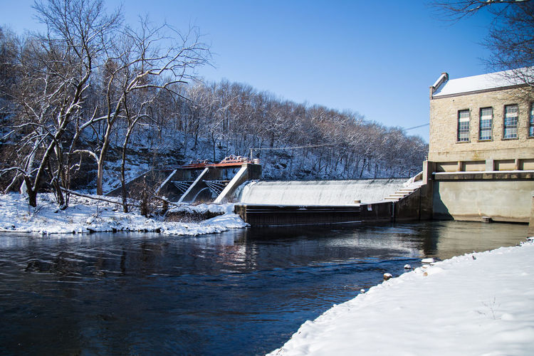 Architecture Building Exterior Built Structure Cold Cold Temperature Dam Day Outdoors Reflection River Snow Water Weather Winter