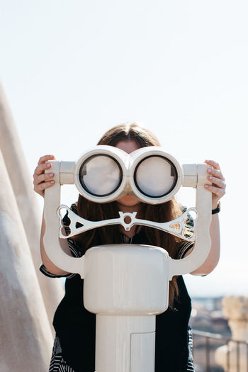 Close-up of woman holding camera against clear sky