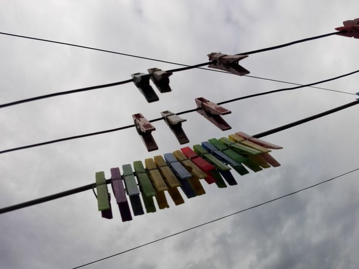 Low angle view of clothespins hanging on rope against cloudy sky