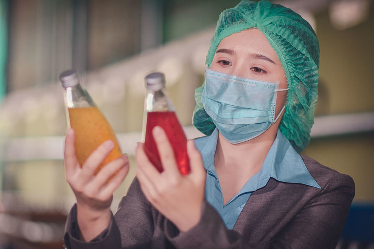 Close-up of woman wearing mask inspecting drinks in factory