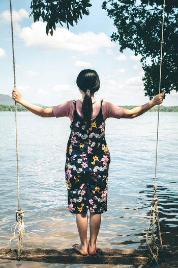 Rear view of woman swinging by lake