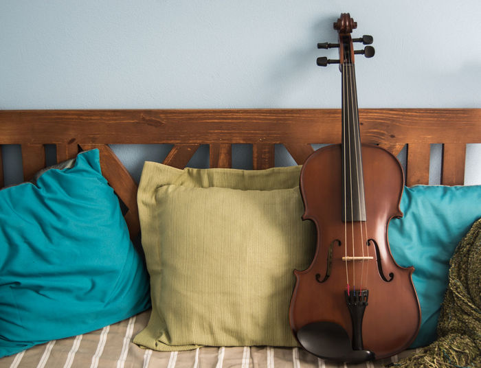 A viola in a couch with cushions. Couch Home Homely Arts Culture And Entertainment Brown Cushions  Home Interior Indoors  Music Musical Equipment Musical Instrument Seat Seats String Instrument Viola Violin Wood - Material
