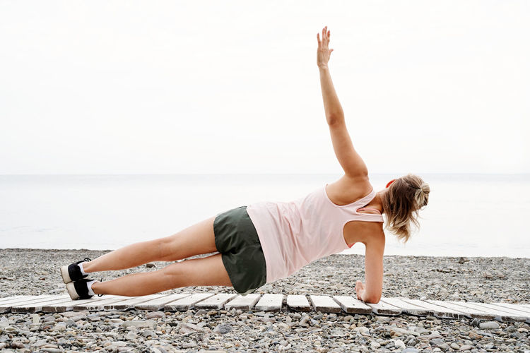 Full length rear view of woman exercising on beach against sea