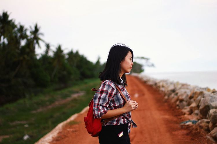 Young woman looking away while standing on land against sky