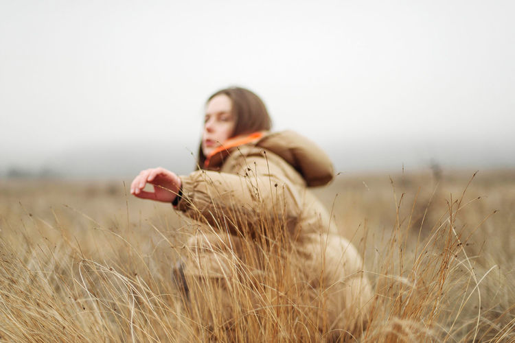 Side view of young woman lying on field against sky