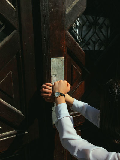 Close-up of woman with wristwatch touching door