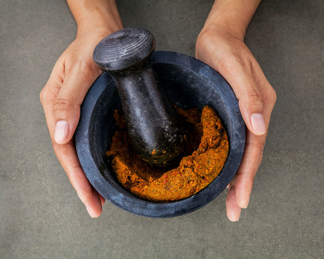 Directly above shot of hand holding spice in mortar