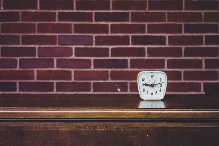 Close-up of alarm clock on table against brick wall