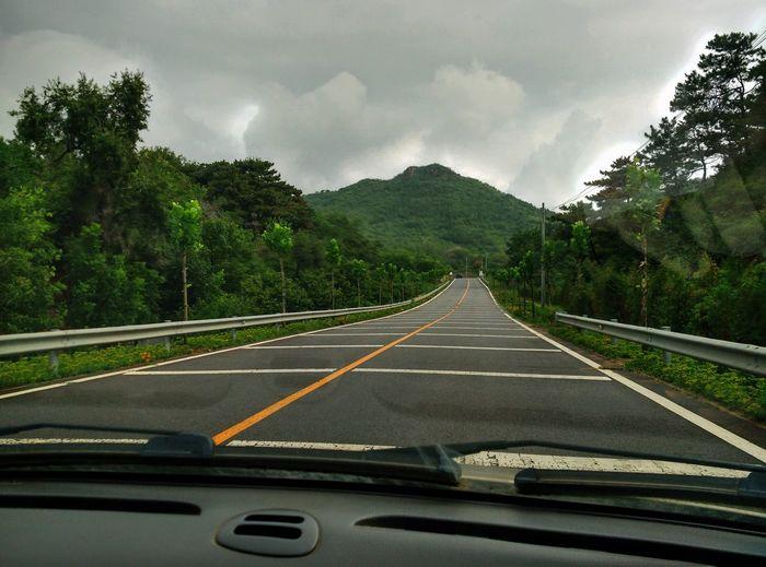 Road Leading Towards Mountain Seen Through Car Windshield