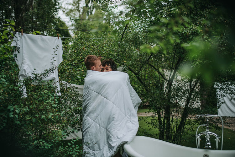 Couple with towel standing against trees