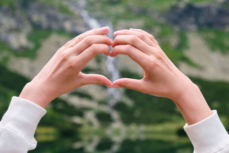 Close-up of hand making heart shape outdoors