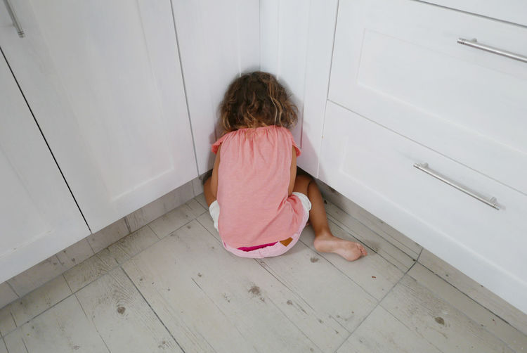 Rear View Of Girl Hiding In Kitchen