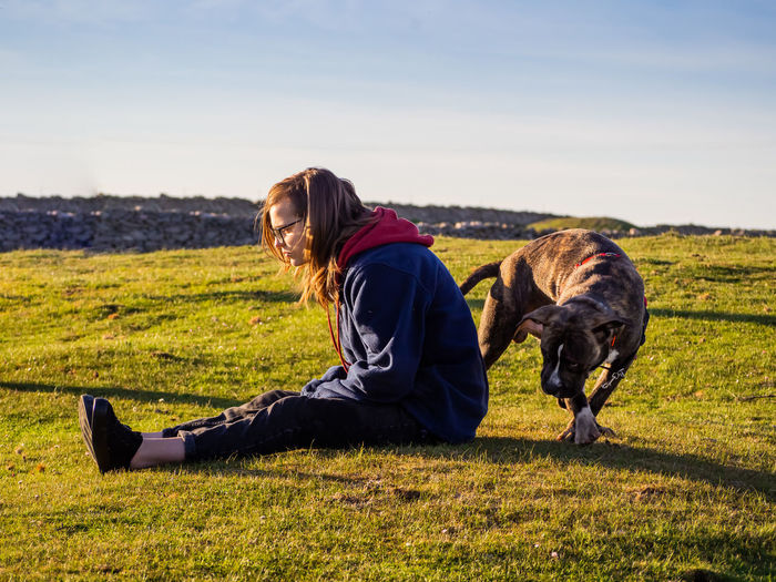 Girl with dog sitting on grass against sky
