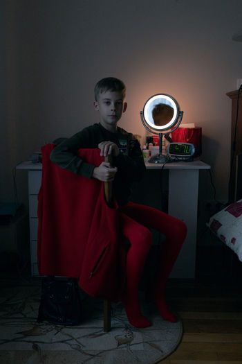 One Person Full Length Indoors  Home Interior Red Child Males  Lifestyles Sitting Domestic Room Childhood Boys Men Holding Home Casual Clothing Real People Leisure Activity Flooring Innocence