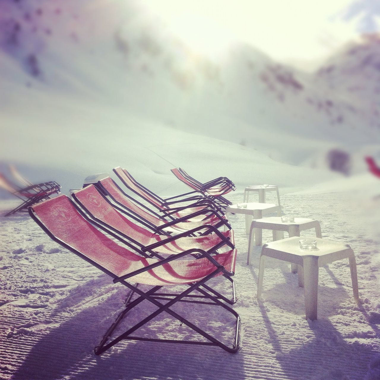 Deck chairs on snow covered landscape
