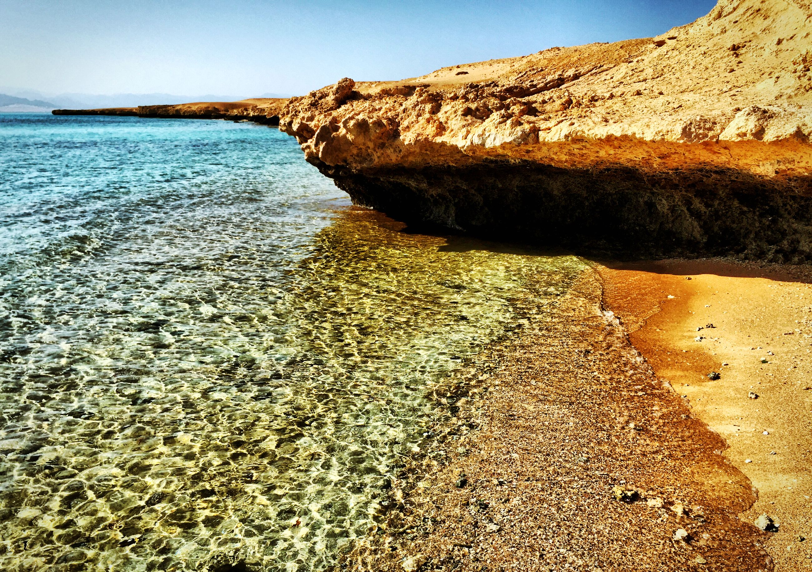 sea, water, beach, shore, tranquility, tranquil scene, sand, horizon over water, scenics, nature, clear sky, blue, beauty in nature, coastline, sky, sunlight, day, idyllic, rock - object, outdoors