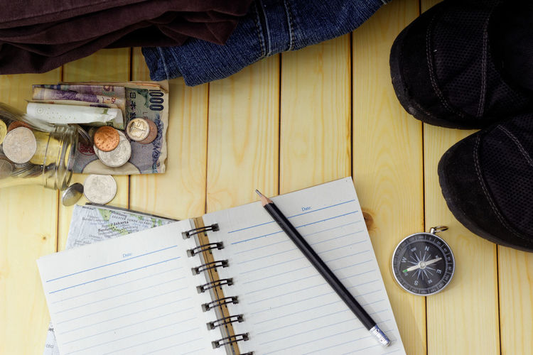 Travel and vacation plan concept Travel Holiday Holidays Vacation Plan Copy Space Copyspace Compass Cloth Jacket Map Wooden Background Pencil Blank Book Directly Above Paper High Angle View Note Pad Wood - Material Table Writing Close-up Tourism Spiral Notebook Sketch Pad Lined Paper