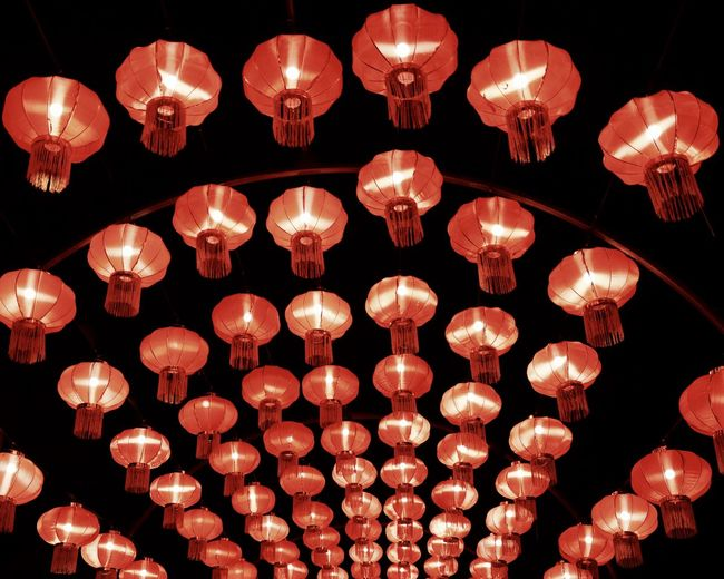 Low angle view of illuminated lanterns hanging at night