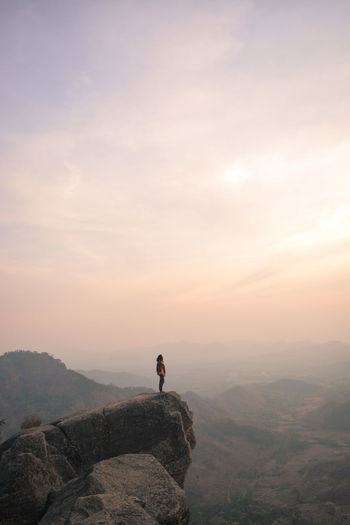 Young man standing on mountain against sky during sunset