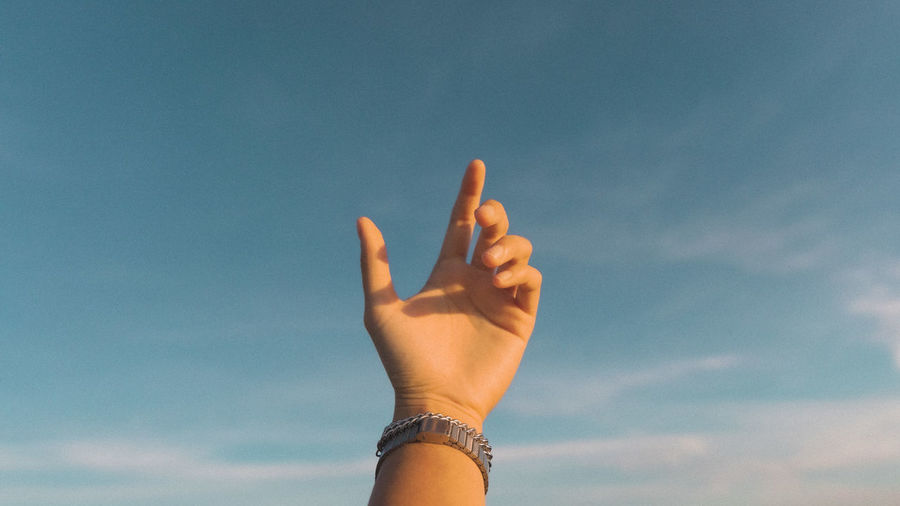 Low angle view of woman hand against sky