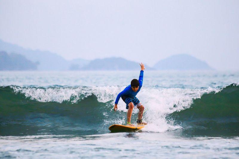 Full length of man surfing on sea against sky